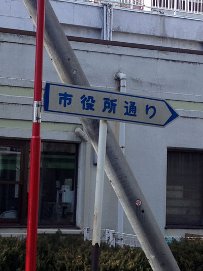 久米川駅北口の交番近くにある市役所通りの道路名称表示板