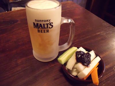 キンキンに冷えたジョッキに入った生ビールと定番のお通し、野菜スティック